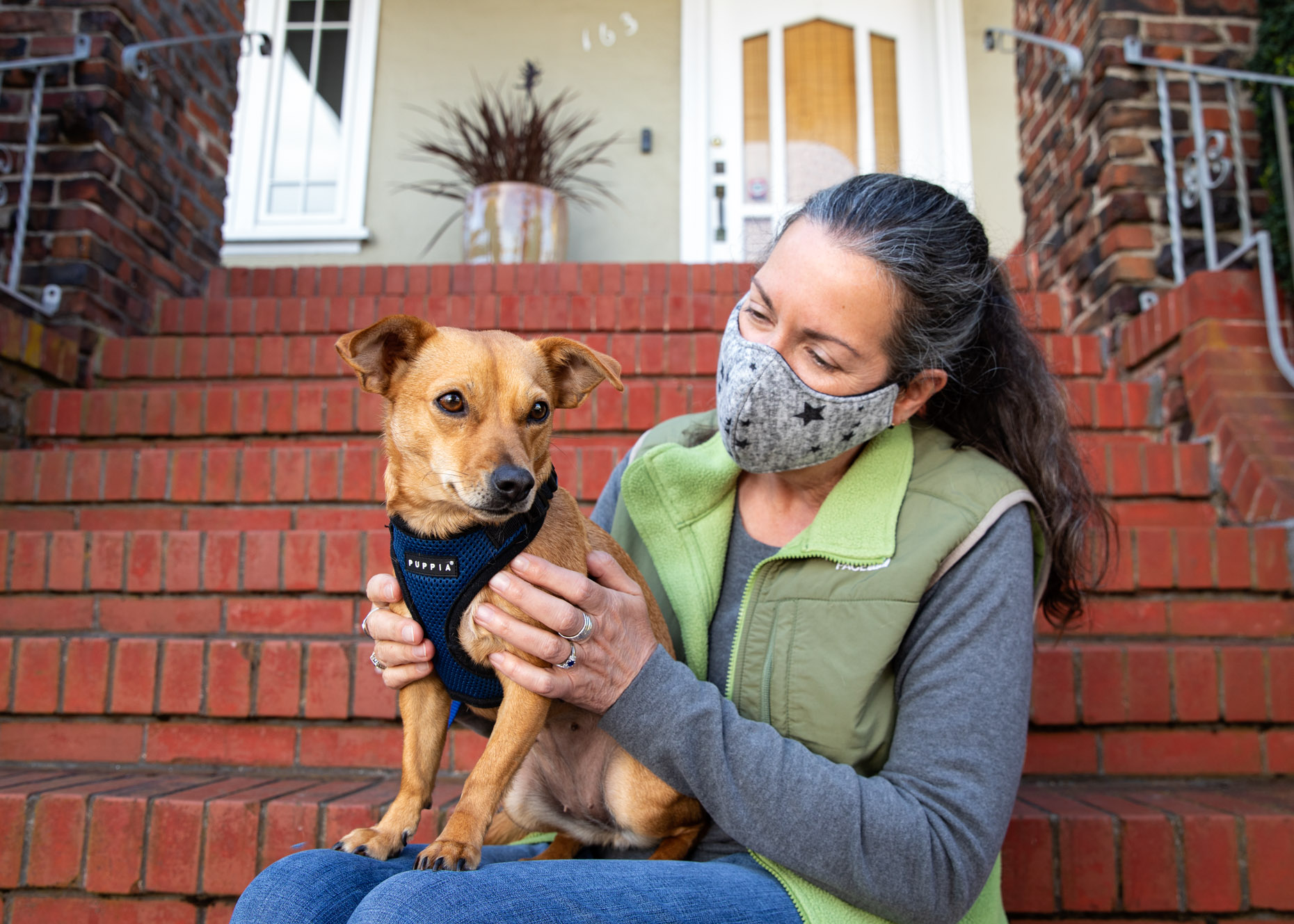 middle-aged woman wearing face mask and holding a chihuahua mix dog on front steps of her house